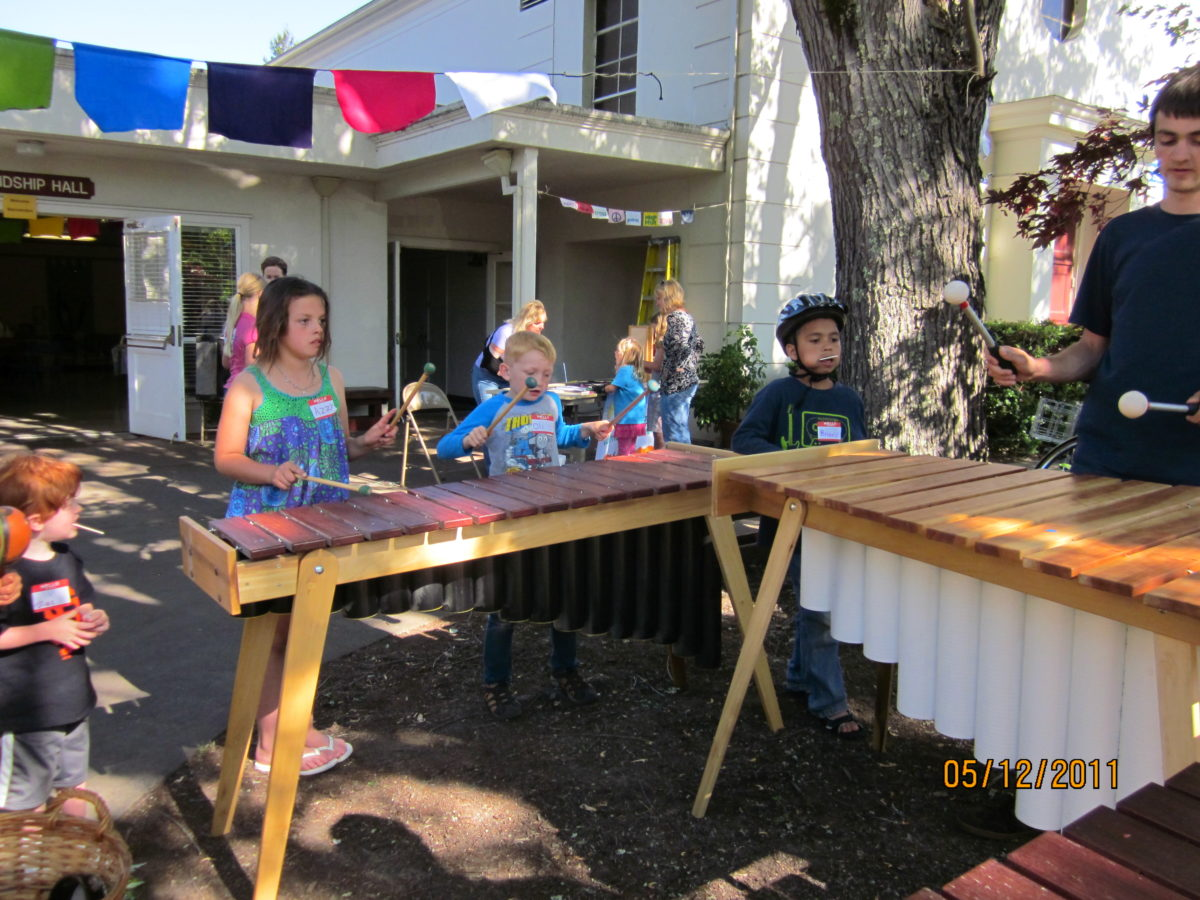 neighborhood kids of all ages play around on marimbas handmade by another neighbor
