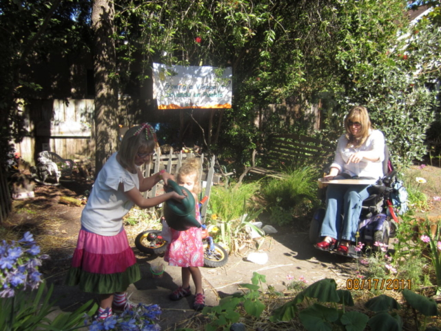 watering the pumpkins in the community space while mom and sister look on